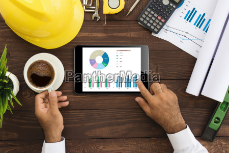 engineer using tablet checking business graph