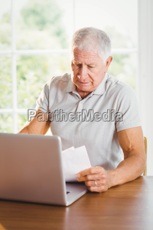 senior man holding sheets and using