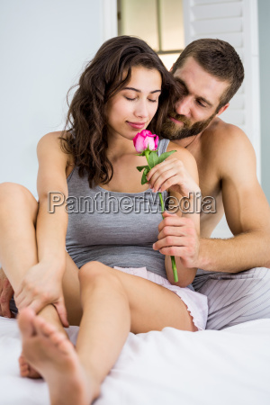 man offering a rose to woman