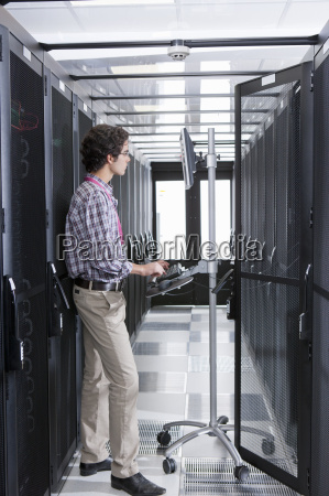 technician working on computer in aisle