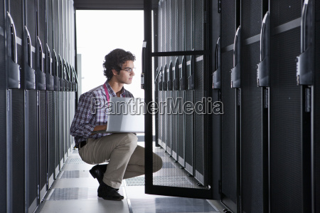 technician kneeling with laptop checking aisle