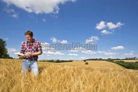 farmer using digital tablet in sunny
