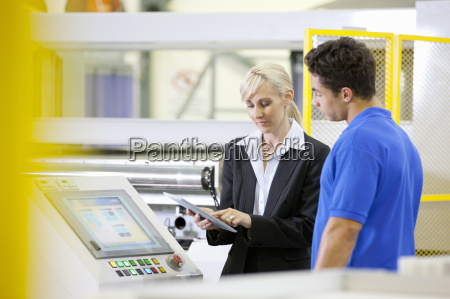manager holding digital tablet talking with