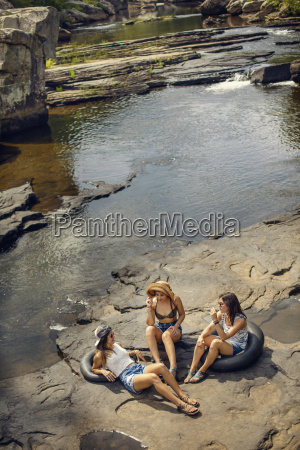 three young women hike and play