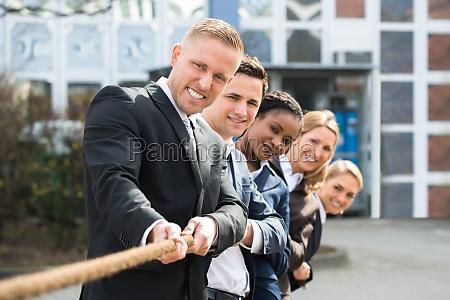 imprenditori multietnici che giocano a tug