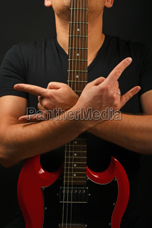 man with red guitar showing devil