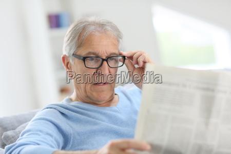 senior uomo a casa lettura giornale