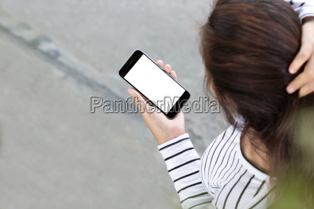 woman looking on phone and walking