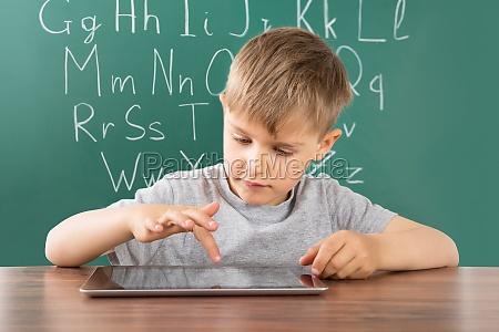 ragazzo con tavoletta digitale a scuola
