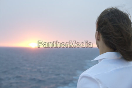young man looking at sunset over