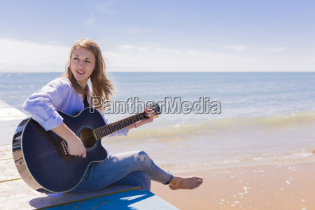 woman playing guitar on jetty