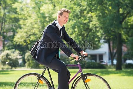 uomo daffari andando in bicicletta nel