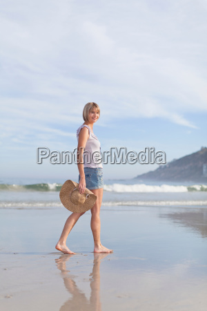 woman carrying straw hat on beach