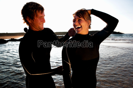 man zipping up laughing womans wetsuit