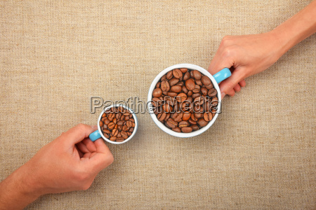 two hands with roasted coffee beans
