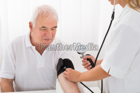 female doctor checking blood pressure of