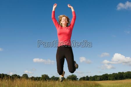 woman jumping in field