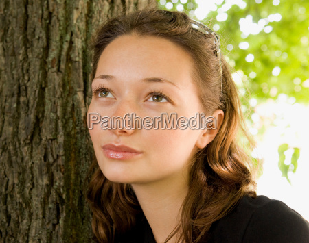 girl leaning against a tree looking