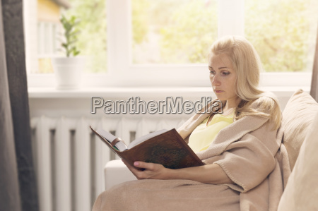 donna appoggiata sul divano e leggere