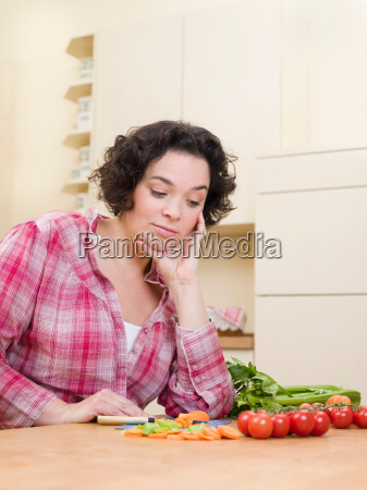 woman looking doubtfully at vegetables