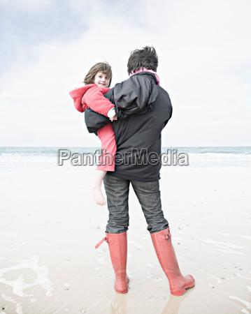 woman holding child on beach