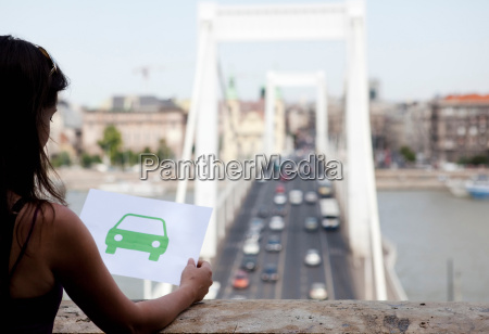 woman holding paper green car