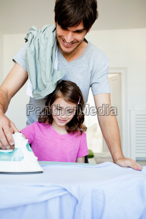 father and girl ironing