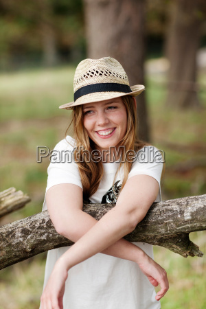 young woman leaning againg tree