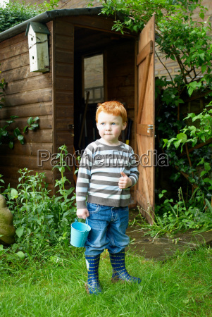 boy playing with bucket in backyard