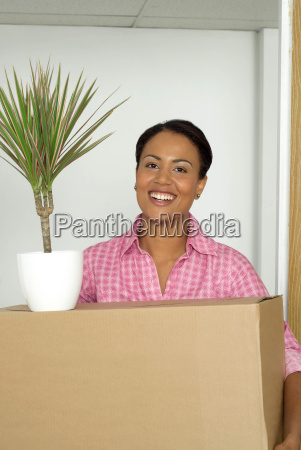 woman carrying box and potted plant