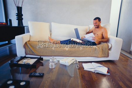 man studying with laptop in living