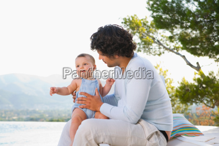 man holding baby outside