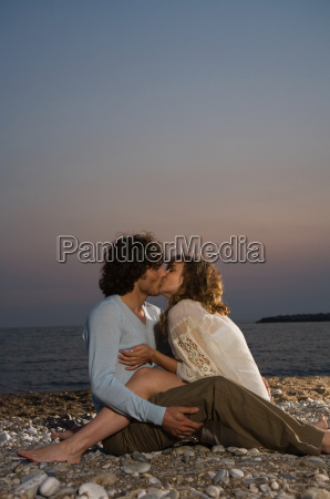 young couple sitting on beach kissing