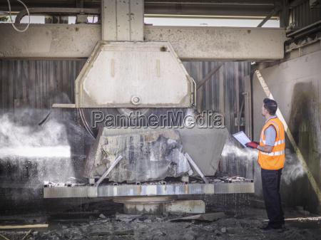 lavoratore cava ispezionando sega pietra
