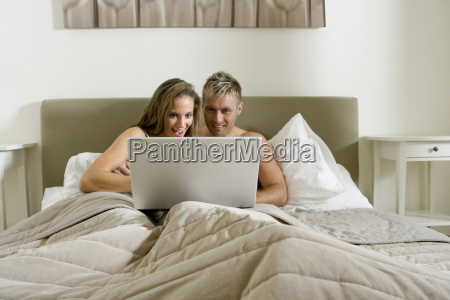 young couple using laptop in bed