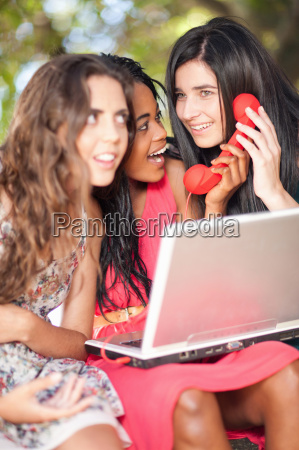 women using laptop and phone whilst