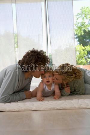 parents kiss babys cheeks living floor