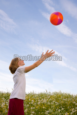 girl in meadow playing ball