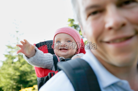 father and baby in backpack hiking