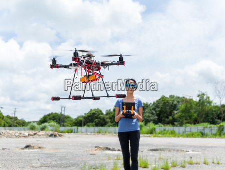 woman remote the flying drone at