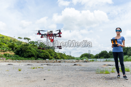 young woman control drone flying at