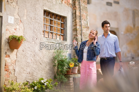 man and woman walking past house