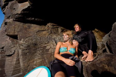 couple sitting on large rocks