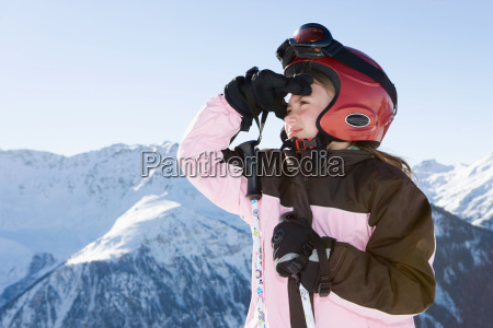 young girl in ski kit looking