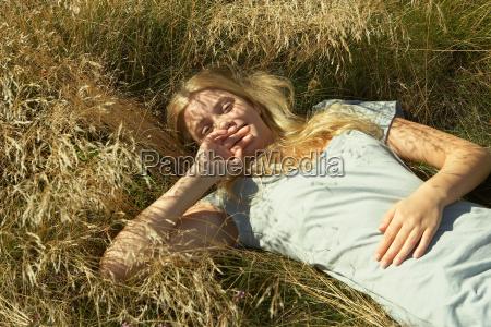 young woman lying in long grass