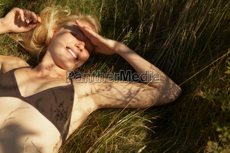 young woman lying in grass