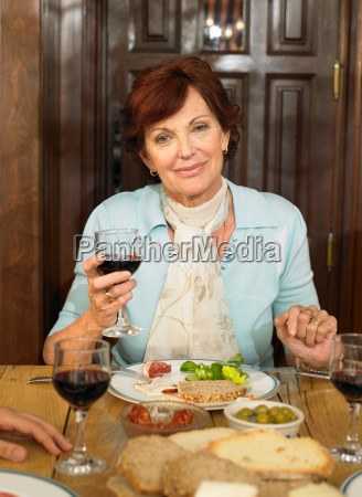 senior woman at table holding wine