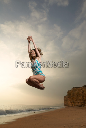 woman jumping with beach background