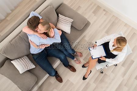 coppia seduta sul divano che abbraccia