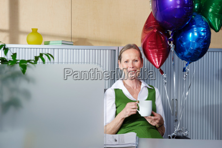 senior woman with balloons at desk